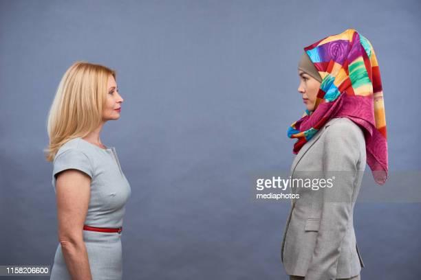 coworking-geschäftsfrauen unterschiedlicher kulturen - kopfbedeckung stock-fotos und bilder