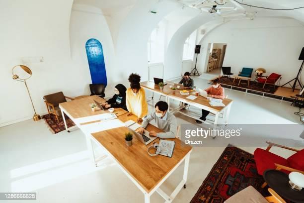 coworking pendant la pandémie de coronavirus - photo grand angle avec l'espace de copie - hijab feet photos et images de collection