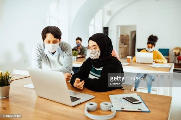 coworking pendant la pandémie covid-19 - femme japonaise et moyen-orientale traitant du nouveau projet - hijab feet photos et images de collection