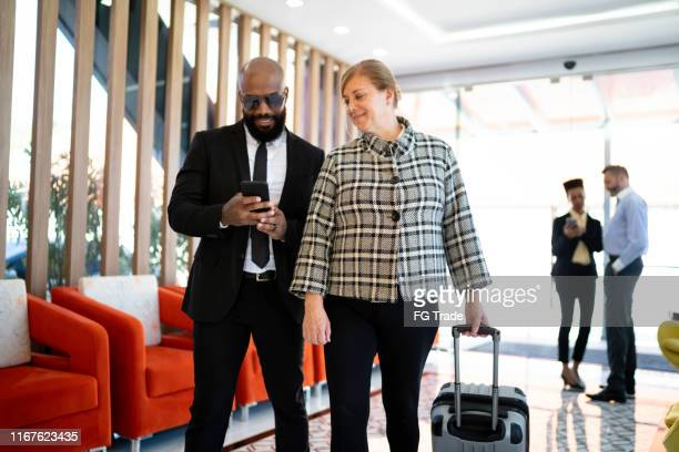 coworking laughing together and using cellphone inside an airport vip lounge - best sunglasses for bald men stock pictures, royalty-free photos & images
