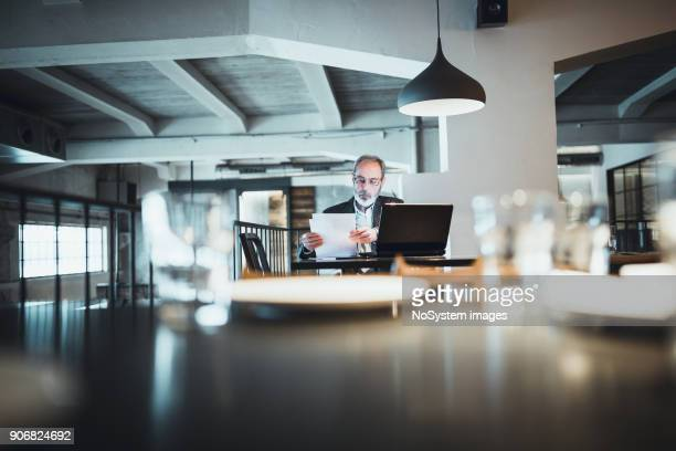 co-working space in high-end restaurants. senior businessman with beard working on laptop in restaurant. - computer system diagram stock photos and pictures