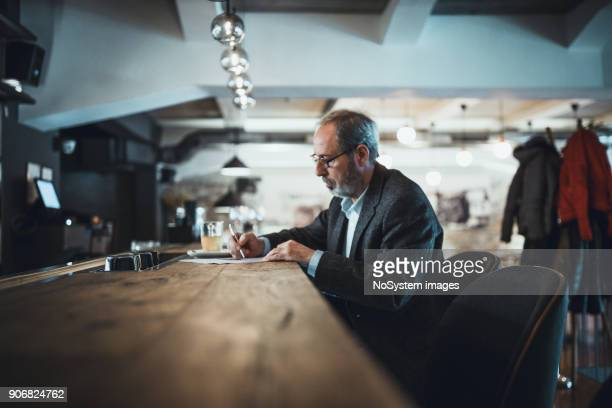 co-working space in high-end restaurants. senior businessman with beard working in high end restaurant - creative director stock pictures, royalty-free photos & images