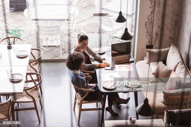 co-working space in high-end restaurants. two female colleagues having business meeting in high end restaurant. - computer system diagram stock photos and pictures