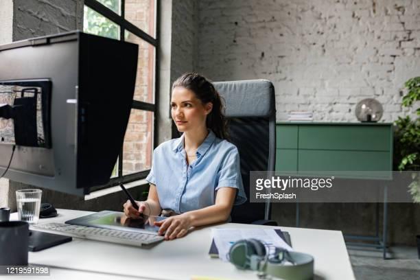 coworking stories: woman graphic designer arbeitet am pc im büro - designberuf stock-fotos und bilder