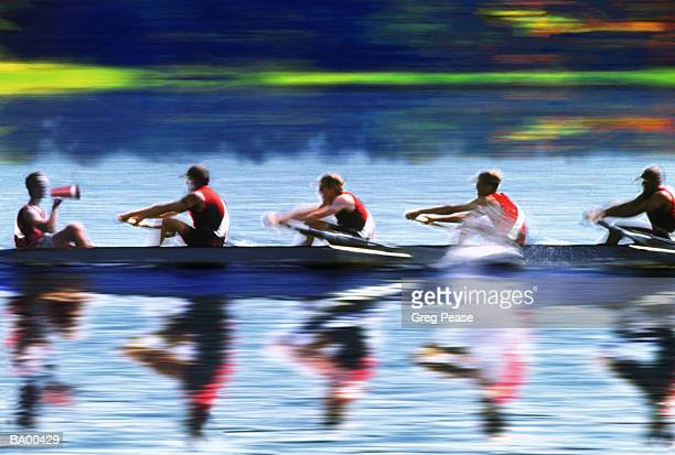 Coxswain leading four man rowing crew (blurred motion)