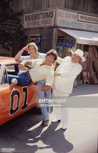 Coy Duke smiles as Vance Duke is dragged out of the 'General Lee' by Jefferson Davis 'Boss' Hogg in a publicity still from the television series 'The...