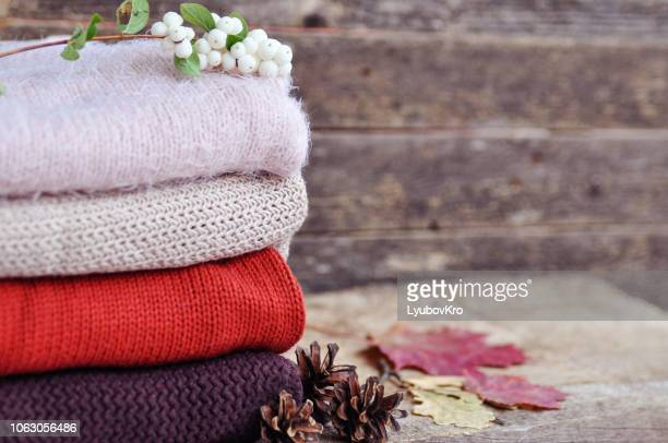 Cozy autumn: knitted clothes, leaves, cones on an old wooden background.