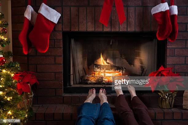 cozy Christmas fireplace with Grandmother and Granddaughter warming feet