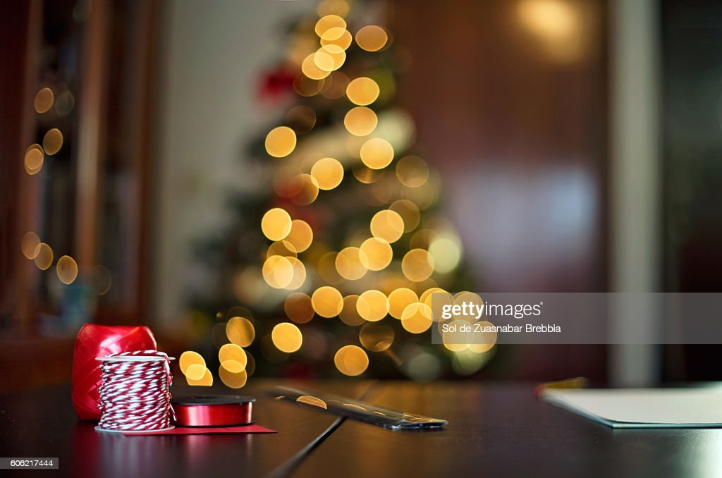 Cozy Christmas. Table with ribbons crafts with Christmas tree behind : Stock-Foto