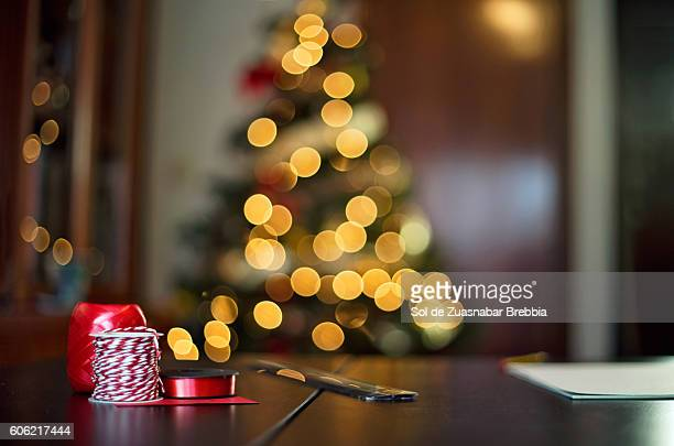 cozy christmas. table with ribbons crafts with christmas tree behind - los tres reyes magos fotografías e imágenes de stock