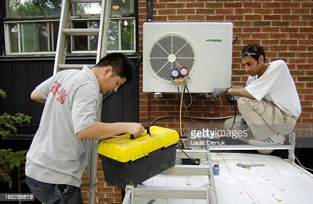 Cozy Comfort subcontractors Bob Chen and Sam Molaei install an air conditioner at the Simek household on Stafford Street in downtown Toronto...