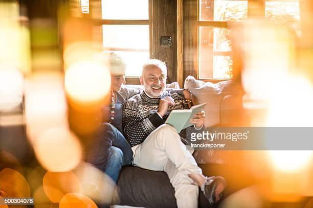 cozy couple on the sofa reading a book for christmas