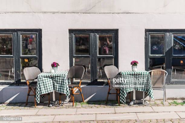 Cozy Danish coffee shop. Small plants decorating a tables outside on a summer morning.