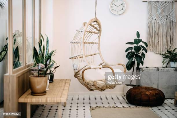 cadeira aconchegante pendurada na sala de estar loft com design elegante e bohemia. bem projetado e decorado com uma variedade de plantas interessantes - decoration - fotografias e filmes do acervo