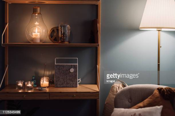 cozy home interior shelf with candles and bluetooth wireless speaker - bluetooth stock pictures, royalty-free photos & images