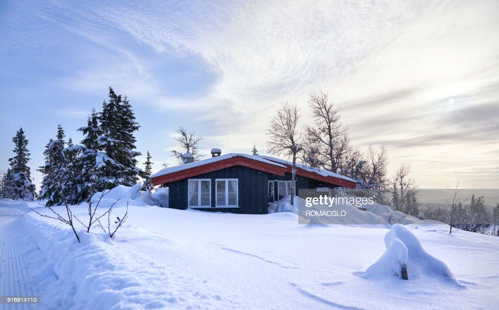 Gemütliche Berghütte mit tiefem Schnee und Schneeflocken in der Luft, County Norwegen Oppland : Stock-Foto