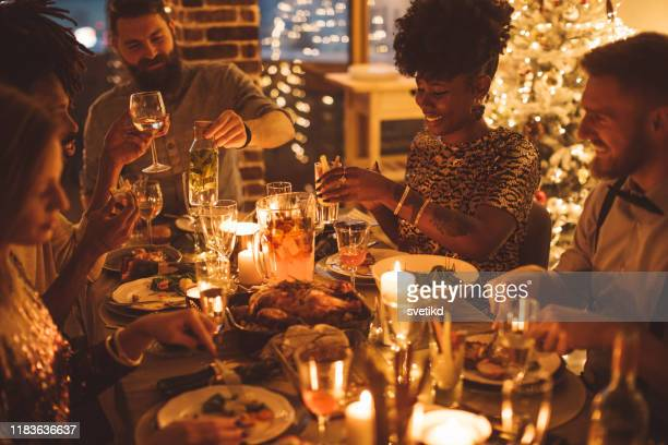 cozy new year dinner among friends - evening meal stock pictures, royalty-free photos & images