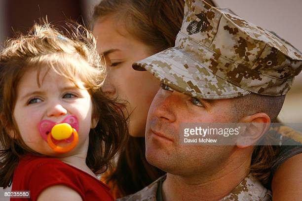 Cpl Matthew Alford holds his 20-month-old daughter Aubrey and wife Tara-Sky Alford before he and other Marines and Sailors of the 1st Air Naval...