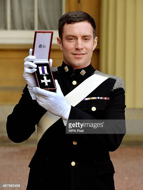 Cpl Oliver Bainbridge of the Royal Dragoon Guards holds his MC after it was presented to him by the Prince of Wales during a Investiture ceremony at...