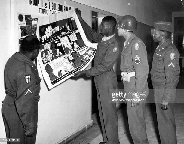 Cpl Roy Harris places a poster in the hall of quarters of the 594th Transportation Truck Company displaying a feature of the Army's new career...