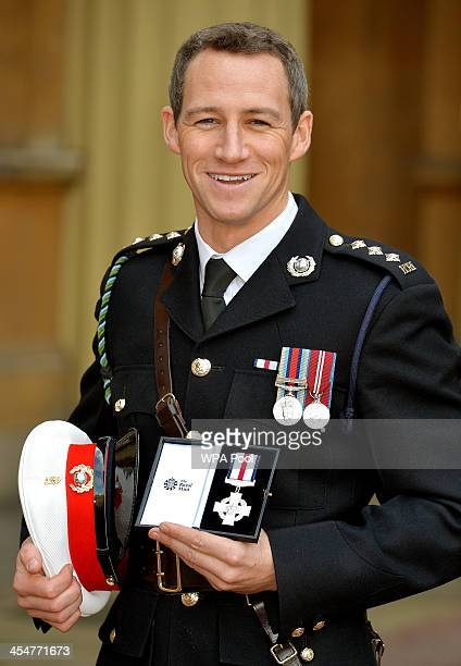 Cpt James Glancy of the Royal Marines holds his Conspicuous Gallantry Cross after it was presented to him by Queen Elizabeth II at an Investiture...