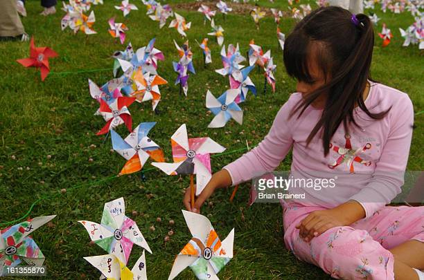 AURORA CO SEPTEMBER 21 2005 <cq> 7yearold Evelyn Saldivar places a pinwheel for peace in the lawn of Vassar Elementary School 18101 E Vassar Place...
