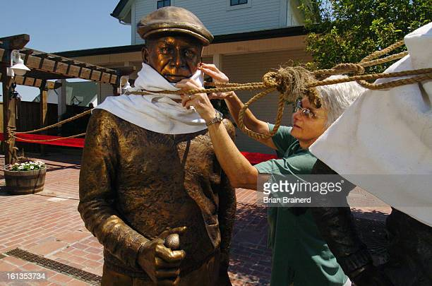 Cq> Sculptor Nancy Golden adjusts her figure of Ben Hogan after placing it at Murphy Creek Golf Course Thursday and securing it with rope until it...