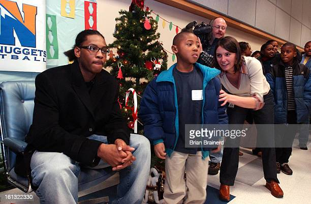 DENVER CO DEC 15 2003 <cq>9yearold<cq> Robert James Cook <cq>gets lined up for a photo with Denver Nuggets' rookie<cq> Carmelo Anthony <cq> who was...