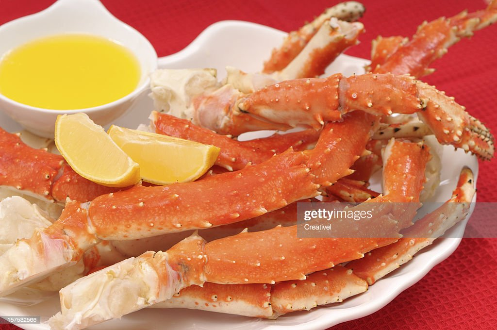 Crab legs served with lemon and butter : Stock Photo
