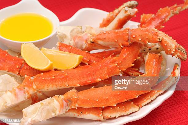 crab legs served with lemon and butter - crab stock photos and pictures