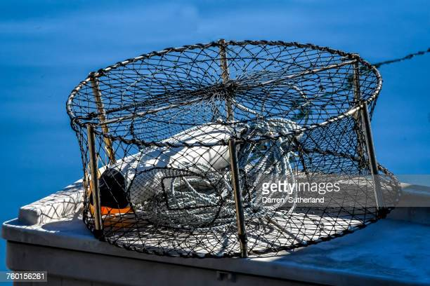 crab pot on a wall by the sea - crab pot stock photos and pictures
