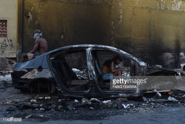 A crack addict smokes crack in a disused and burnt out car in the Sem Terra favela in Complexo da Mare Rio de Janeiro on April 25 2019