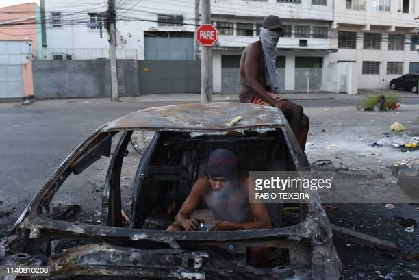TOPSHOT A crack addict smokes crack in a disused and burnt out car in the Sem Terra favela in Complexo da Mare Rio de Janeiro on April 25 2019
