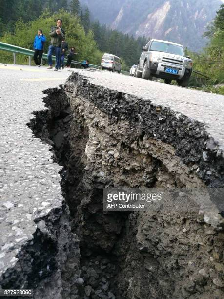 A crack caused by an earthquake is seen on a road in Jiuzhaigou in China's southwestern Sichuan province on August 9 2017 At least 12 people were...