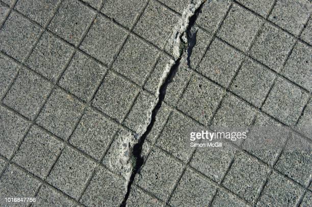 crack in a checkered-patterned concrete footpath - crack imagens e fotografias de stock