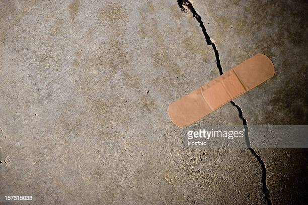 crack in concrete with band-aid on top - band aid stock pictures, royalty-free photos & images