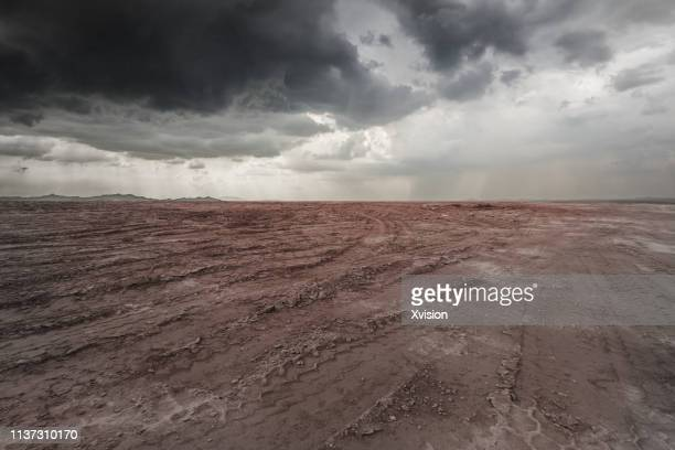 crack land under black cloud - árido fotografías e imágenes de stock