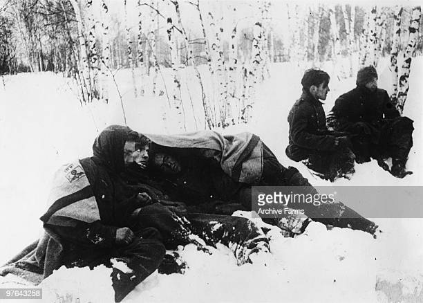 Crack Nazi soldiers are seen huddling close together after their capture to keep warm until they are marched away to prison camp during the Russian...