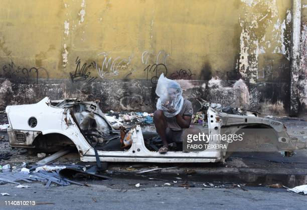 TOPSHOT A crack smokes crack beside the shell of a disused and burnt out car in the Sem Terra favela in Complexo da Mare Rio de Janeiro on April 29...