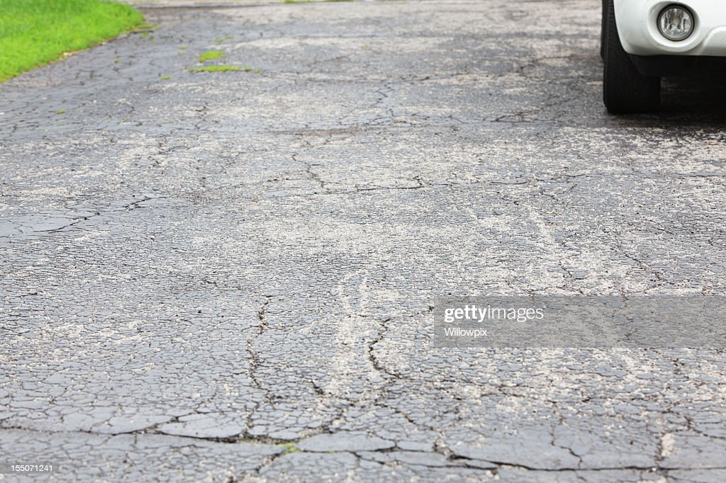 Cracked asphalt driveway with car parked : Stock Photo