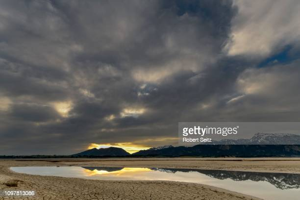 cracked, dry soil with water surface and allgaeu alps in the background, forggensee, fuessen, ostallgaeu, bavaria, germany - stausee stock-fotos und bilder