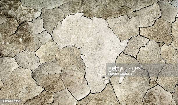 cracked earth in shape of africa - imbalance stock photos and pictures