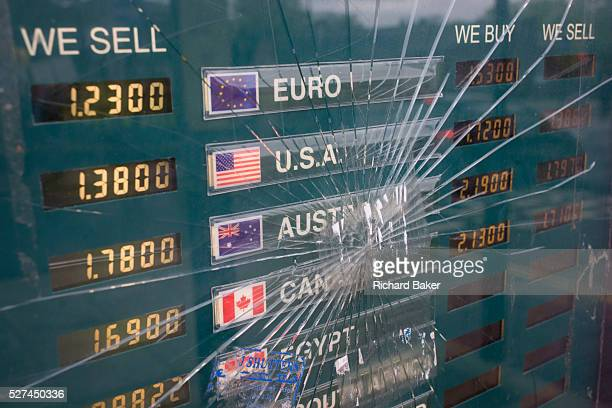 Cracked glass in a foreign currency exchange rates window Currencies from the Eurozone and the USA to Canada and Egypt are displayed in the window of...