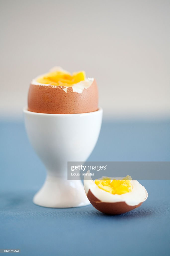 cracked hard boiled brown egg in a white egg cup stock