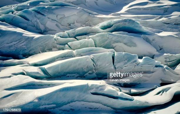 cracked ice covered with snow - clima alpino foto e immagini stock