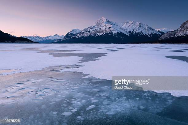 cracked ice on frozen glacial lake, looking towards elliot peak on abraham lake, canadian rockies, alberta, canada - kananaskis country stock pictures, royalty-free photos & images
