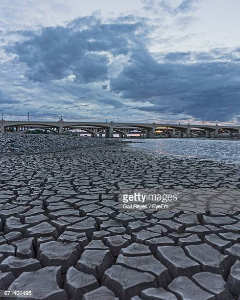 Cracked Lake Bed Against Bridge And Cloudy Sky At Dusk