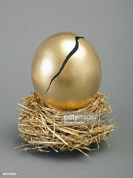 Cracked large gold egg in gold nest