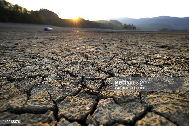 Cracked mud is picture at sunrise in the dried shores of Lake Gruyere affected by continous drought near the western Switzerland village of...