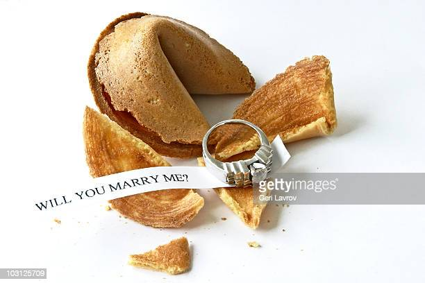Cracked open fortune cookie and diamond ring